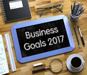 Business Goals 2017 on Small Chalkboard. Business Goals 2017 Handwritten on Blue Small Chalkboard. Top View of Wooden Office Desk with a Lot of Business and Office Supplies on It. 3d Rendering.